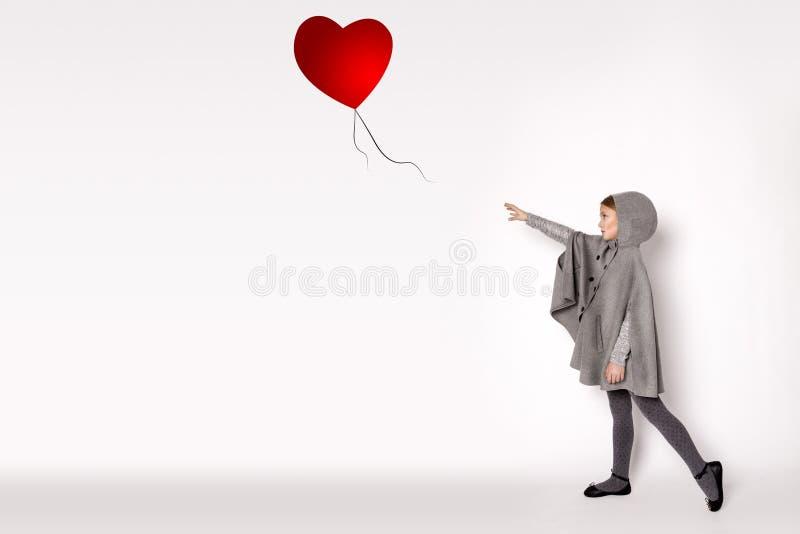 害怕的小女孩在白色背景站立并且在气球以后提供他的手 免版税库存照片