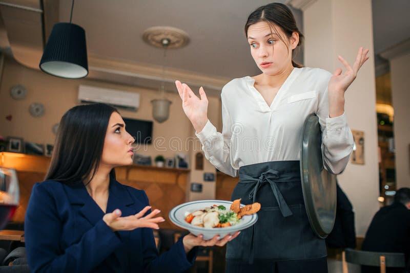 害怕的年轻女服务员看看色拉盘深色的举行在手上 她显示她的这食物 女衬衫的年轻女人是 免版税库存图片