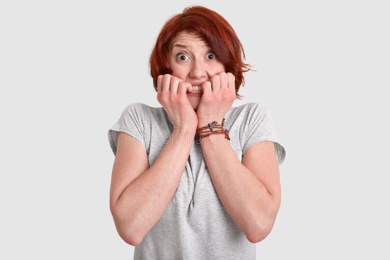 害怕红发妇女照片咬住手指钉子,与紧张的表示的神色,困难afraids,穿戴  免版税库存图片