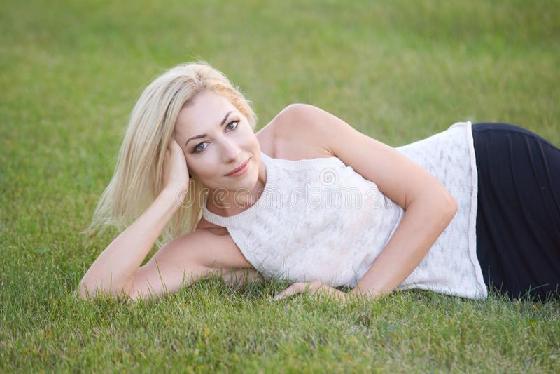 害怕表面女孩纵向惊奇的年轻人 草 夏天照片 白肤金发 愉快的微笑 库存图片