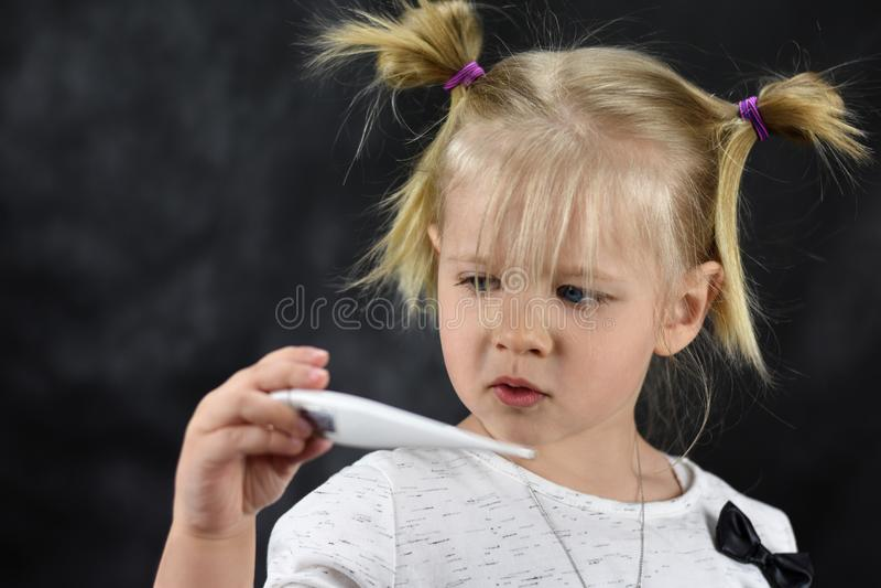 害病的女孩孩子在手中看温度计 免版税库存照片