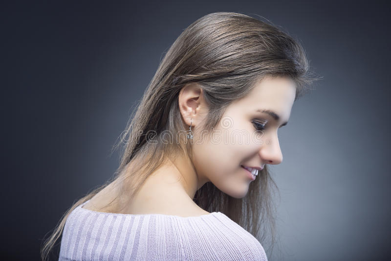 害羞和肉欲的年轻白种人深色的妇女画象有美丽的长的头发的 摆在反对黑色 图库摄影