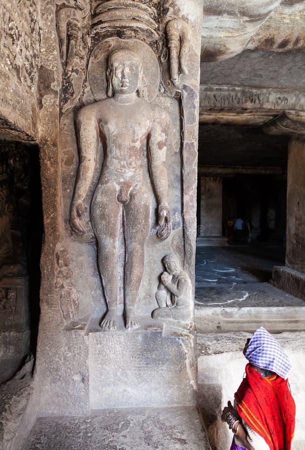 害羞地看赤裸海尼亚的一个古老雕象年轻女人 免版税库存照片