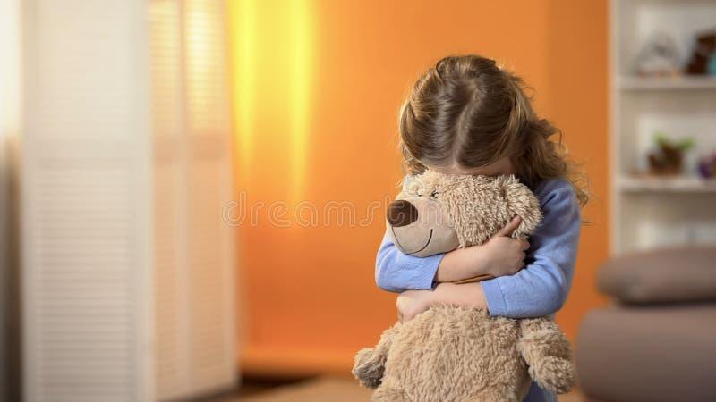 害羞的卷曲在喜爱的玩具熊,童年心理学后的女孩掩藏的面孔 库存图片