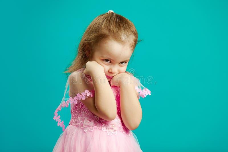 害羞的女孩按她的手面对并且掩藏支持,逗人喜爱的孩子画象蓝色被隔绝的背景的 库存图片