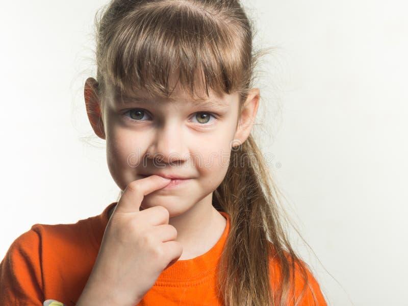 害羞的女孩画象有手指的在白色背景的嘴 免版税库存照片