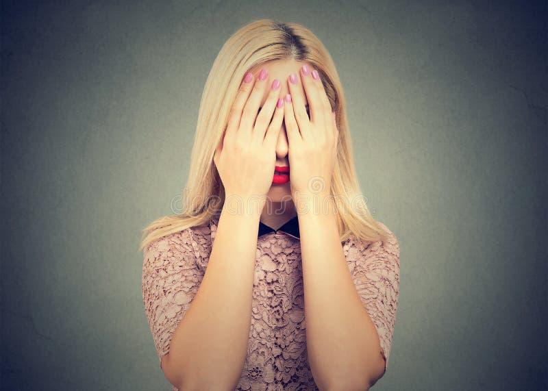 害羞的女孩覆盖物眼睛用手 库存照片