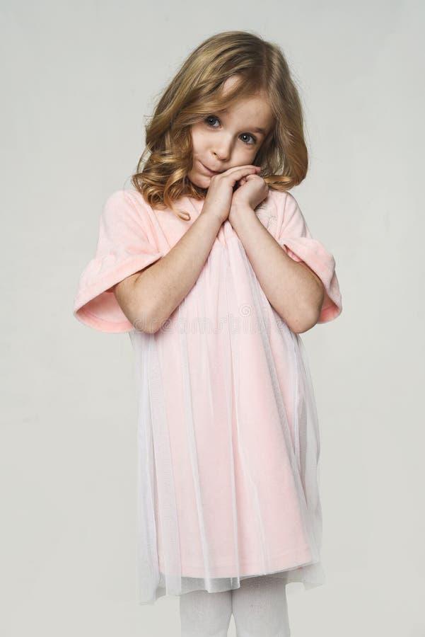 害羞的女孩 逗人喜爱的桃红色礼服的europeoid白肤金发的女孩画象  美丽的c 图库摄影