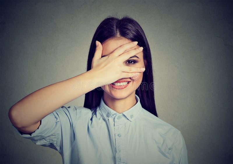 害羞的妇女掩藏的面孔笑怯懦 微笑通过手的逗人喜爱的女孩 免版税库存照片