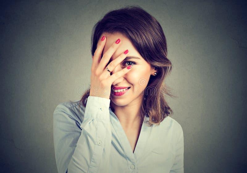 害羞的妇女掩藏的面孔笑怯懦 免版税库存照片
