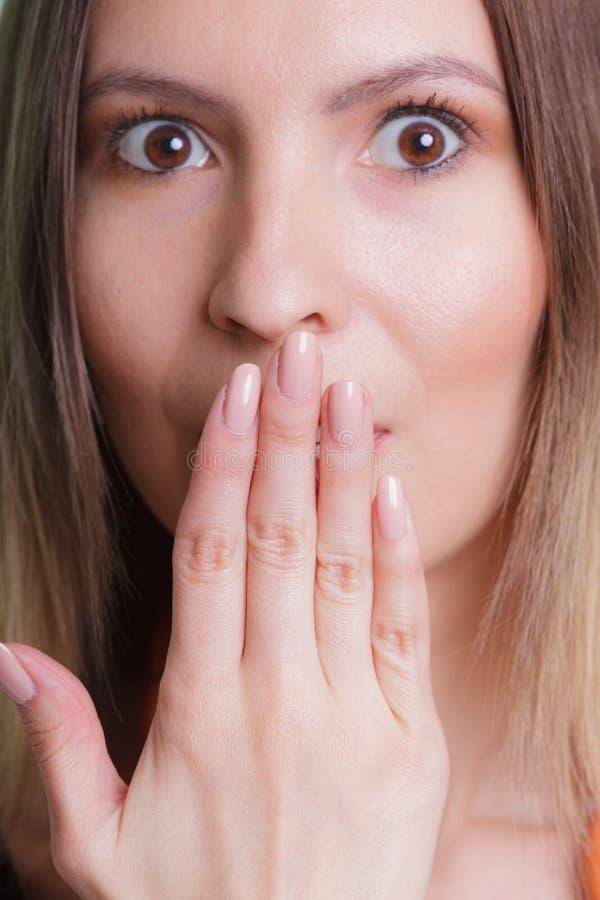 害羞的无语的妇女覆盖物嘴用手 库存图片