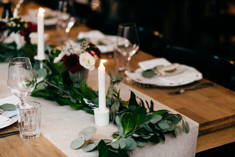 宴会桌设置 板材,叉子,在木桌上的蜡烛与好的装饰 利器和酒杯 餐馆舒适inte 库存照片