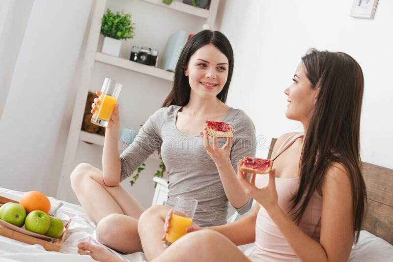 家中卧室里的女同性恋者坐在一旁,举着喝果汁的烤面包 免版税库存照片