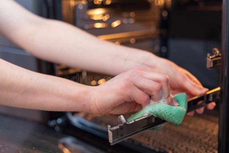 家事和家务概念 洗刷火炉和烤箱 关闭有清洗厨房的绿色海绵的女性手 免版税库存照片