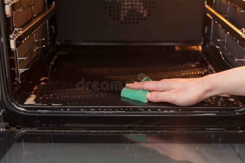 家事和家务概念 洗刷火炉和烤箱 关闭有清洗厨房o的绿色海绵的女性手 免版税库存图片