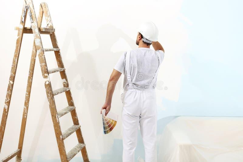 画家人在与颜色样片样品一起使用,壁画 免版税库存图片