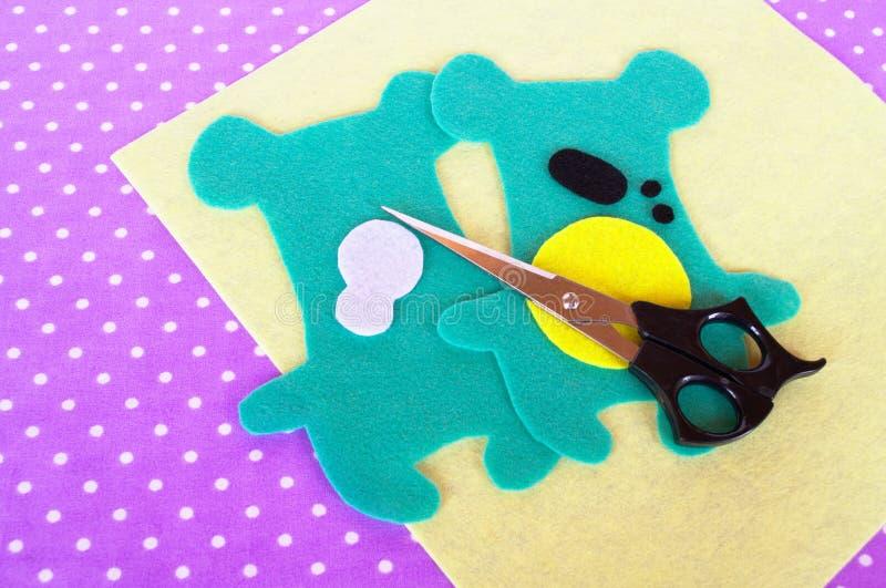 家做的毛毡绿色动物成套工具,在紫罗兰色背景的剪刀与圆点 孩子的缝合的项目 步骤 图库摄影