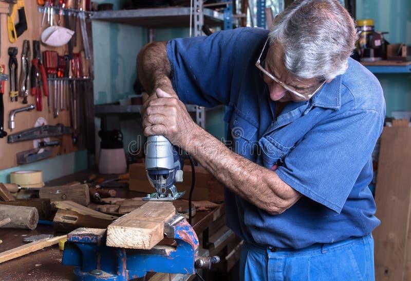 家具木工与木头一起使用在车库a的工作凳看见了 免版税库存照片
