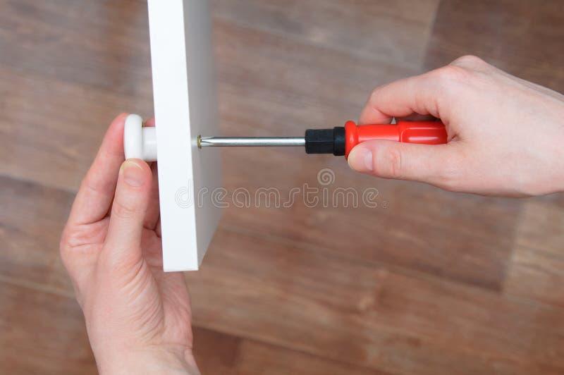 家具汇编 女孩关闭的手 螺丝刀紧固白色瘤对橱门 免版税库存图片