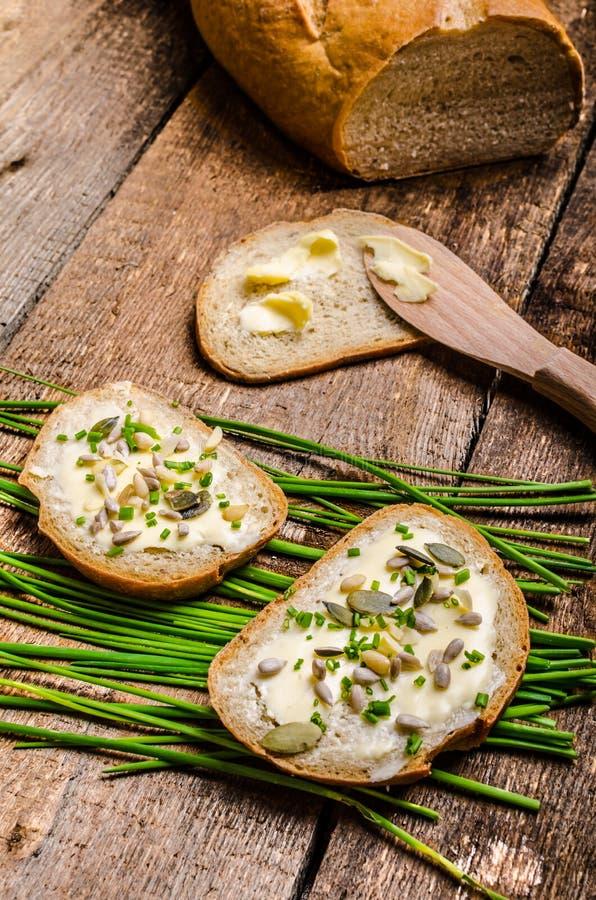 家制面包涂了黄油与健康种子和草本 图库摄影