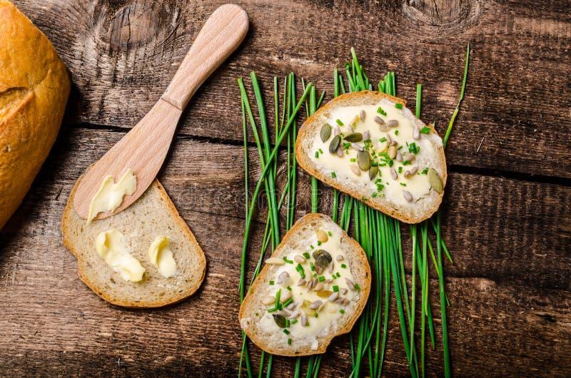 家制面包涂了黄油与健康种子和草本 库存照片