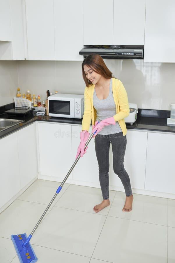 家务和清洁概念,抹尘土的桃红色橡胶手套的愉快的年轻女人使用拖把,当在家时清洗在地板上 图库摄影