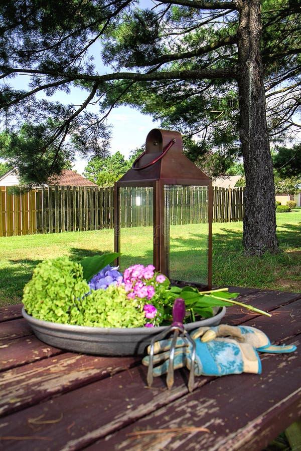 家后院有园艺工具的在与花的野餐桌上 免版税库存图片