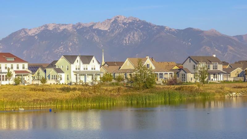 家和反射性湖有山背景 图库摄影