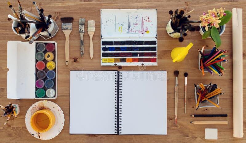 画家工作场所的顶视图 有水彩、水彩画和树胶水彩画颜料五颜六色的油漆调色板的木书桌爱好的 免版税库存照片
