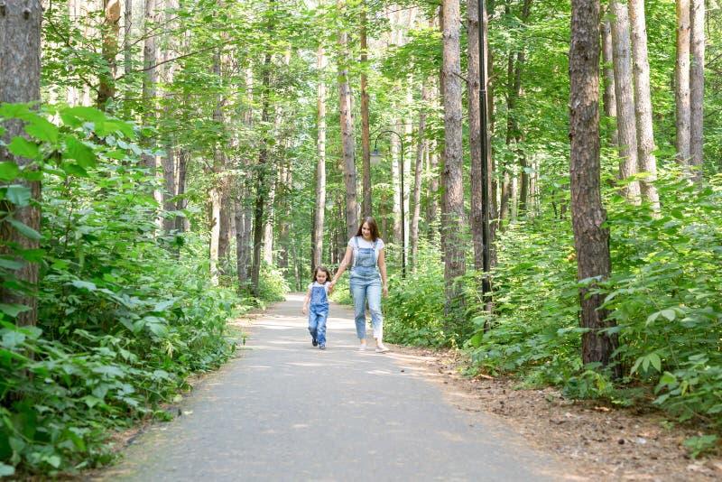 家庭、休闲和自然概念-母亲画象有她的走在绿色公园的小女儿的在夏天 库存图片