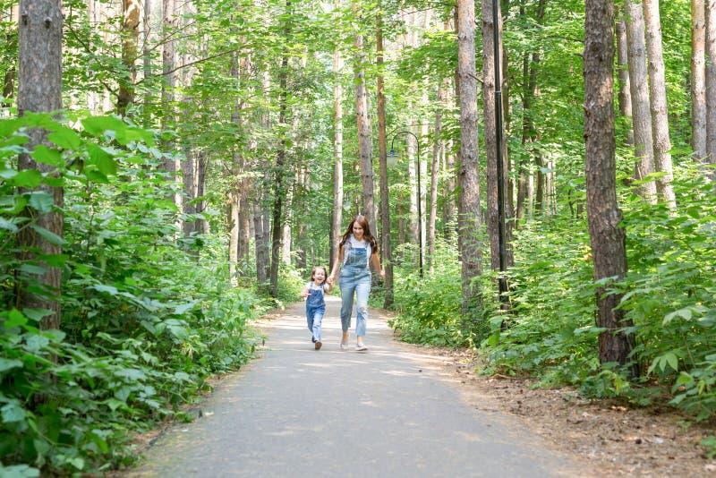 家庭、休闲和自然概念-母亲画象有她的走在绿色公园的小女儿的在夏天 免版税库存照片