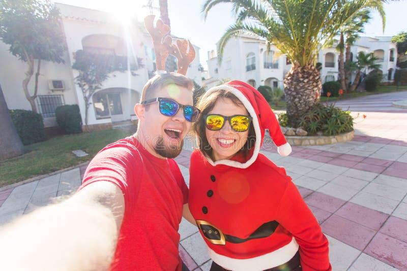 家庭、假日和圣诞节概念-在圣诞老人的愉快的夫妇打扮一起采取selfie 图库摄影