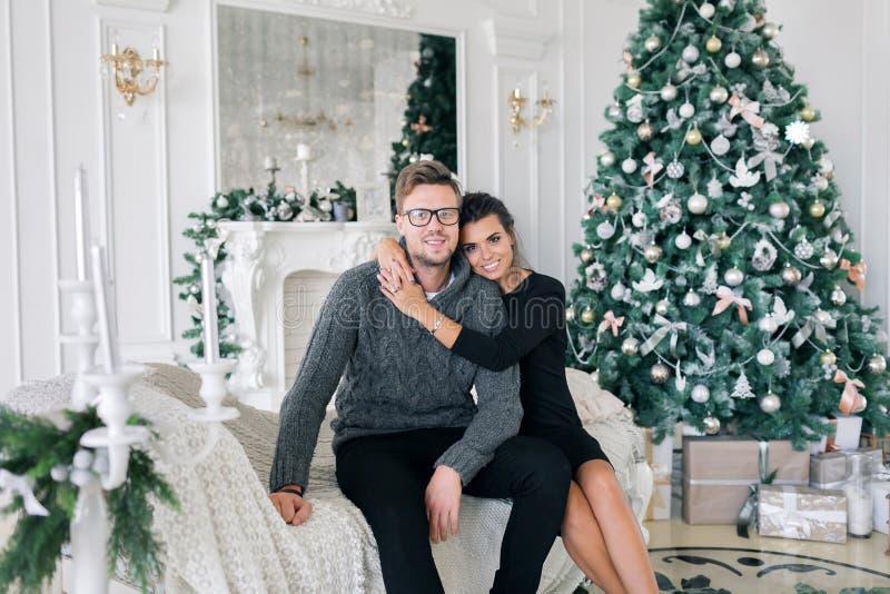家庭、圣诞节、假日、爱和人概念-愉快的夫妇在家坐沙发 免版税图库摄影