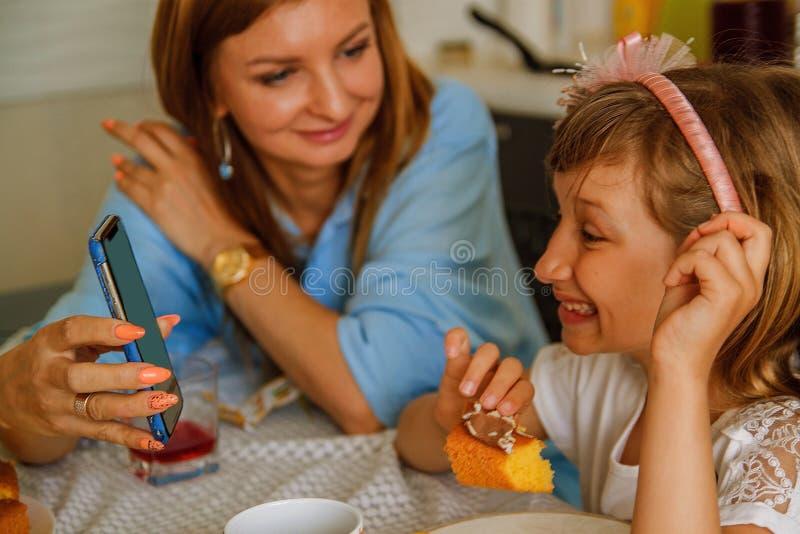 家庭、在家吃和人概念-愉快的母亲,食用的父亲和的女儿早餐 免版税库存图片