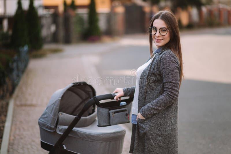 家庭、孩子和父母身分概念-有婴儿推车的愉快的母亲在公园 有太阳镜和时髦的灰色的妈妈 库存图片