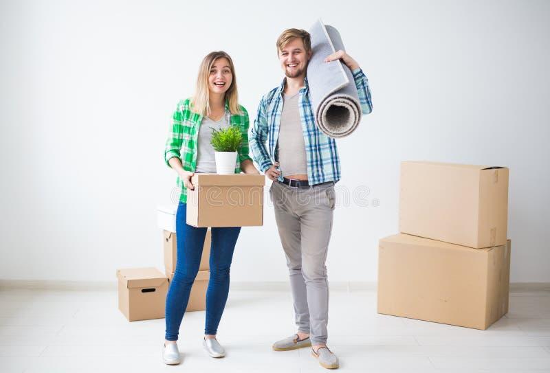 家庭、新的公寓和拆迁概念-移动在新房里的年轻夫妇 免版税图库摄影