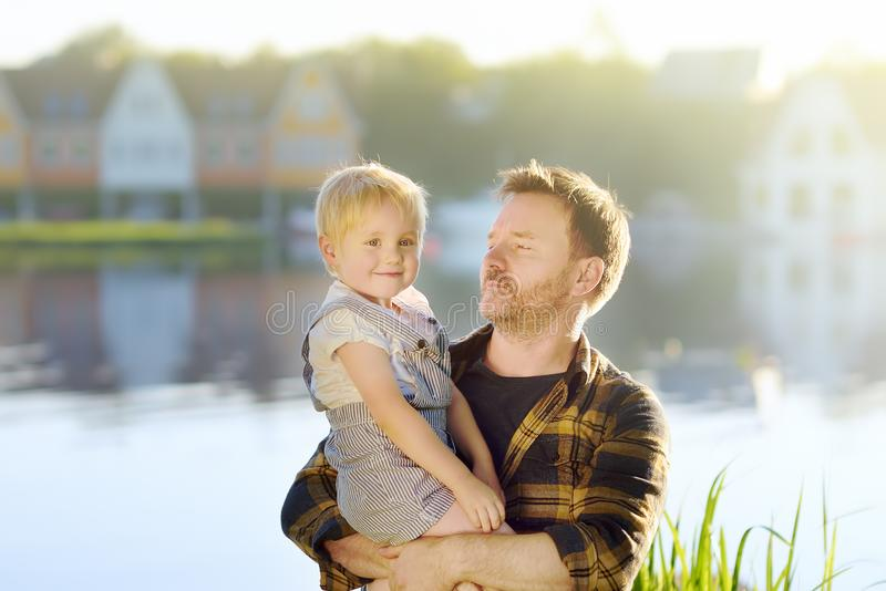 家庭、父亲和小儿子,理想主义的房子背景的湖的 房子梦想  免版税库存图片