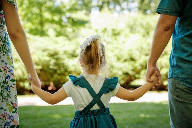 家庭、父母身分、收养和人概念 愉快的走在夏天的母亲、父亲和小女孩停放 免版税库存照片