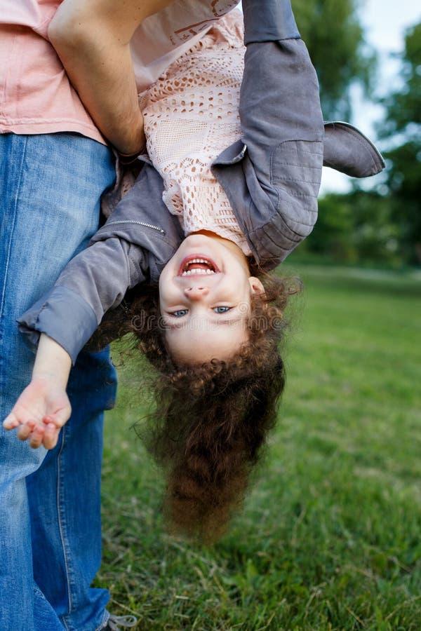 家庭、父母身分、父权和人概念-愉快的人和小女孩获得的乐趣在夏天公园 逗人喜爱的卷曲女孩 库存图片