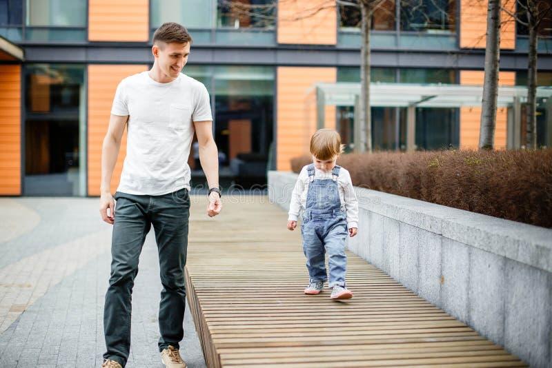 家庭、童年、父权、休闲和人概念-愉快的年轻父亲和小女儿通过t街道漫步 免版税库存照片