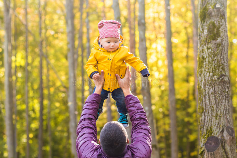 家庭、童年、父权、休闲和人概念-愉快的使用父亲和小的儿子户外 免版税库存图片