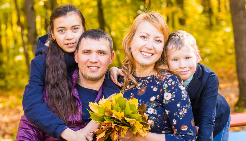家庭、自然、秋天和人概念-愉快的母亲、父亲、儿子和女儿画象秋天的 库存照片