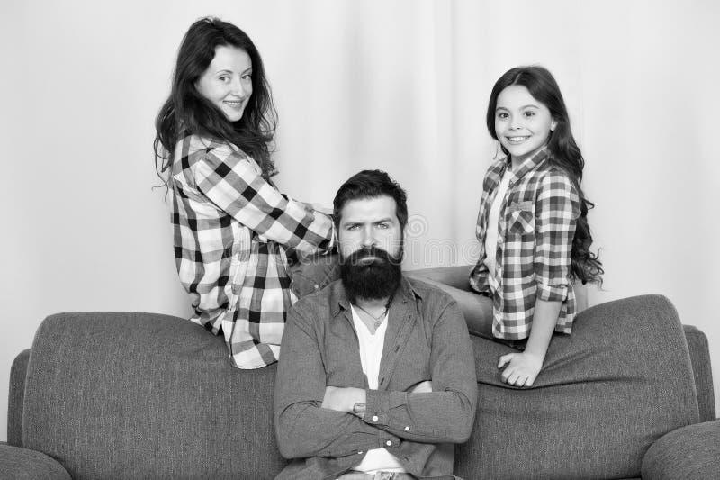 家庭一起度过周末 获得友好的家庭乐趣一起 放松在长沙发的妈妈爸爸和女儿 ?? 免版税库存照片