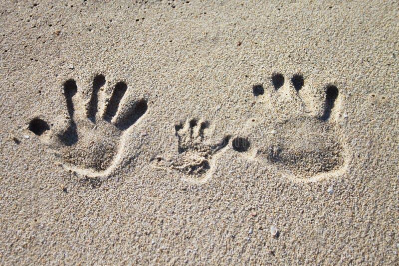 家庭在沙子的棕榈版本记录 免版税库存照片