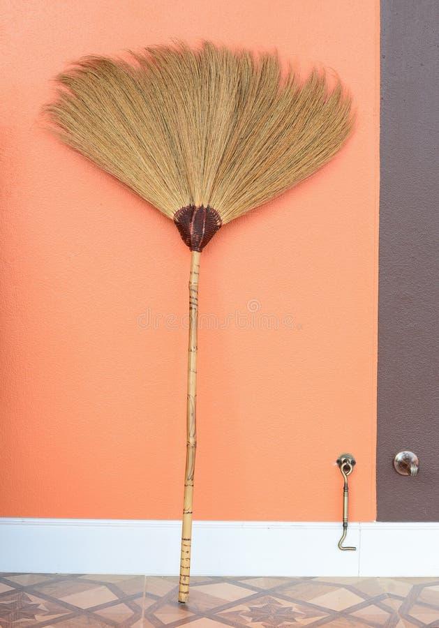 家庭为地板倾斜在橙色w的尘土清洁使用了笤帚 库存图片