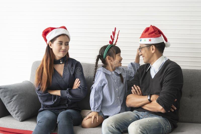 家庭亚裔母亲和父亲有女儿的愉快一起和易怒在客厅在家圣诞节的 免版税库存照片
