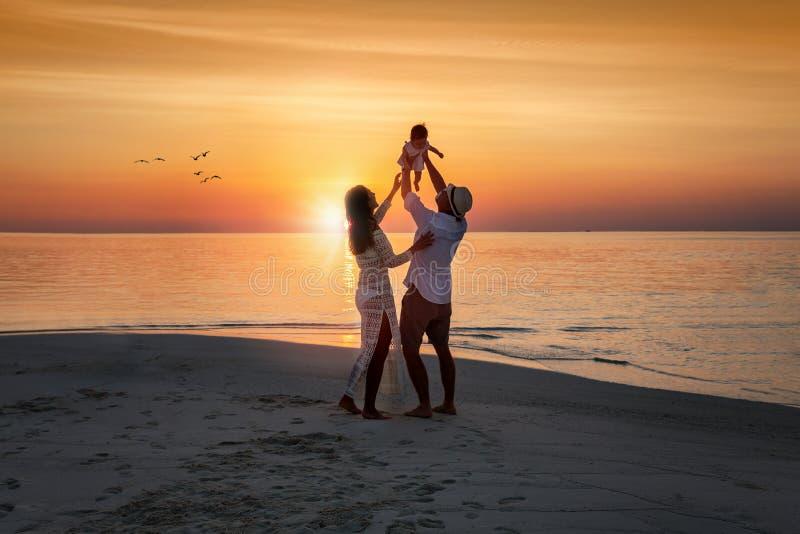 家庭享受他们的在海滩的假期 免版税库存照片
