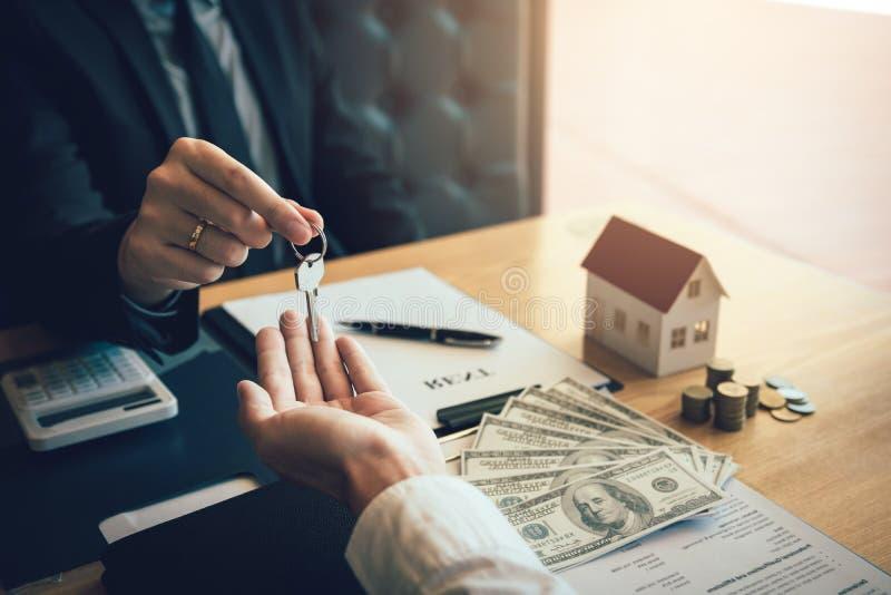家庭代理实施钥匙给在办公室签合同的购房者 免版税库存图片
