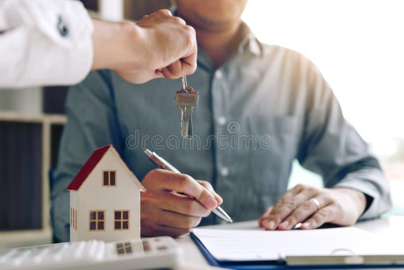 家庭代理实施钥匙给签字的购房者 免版税库存照片