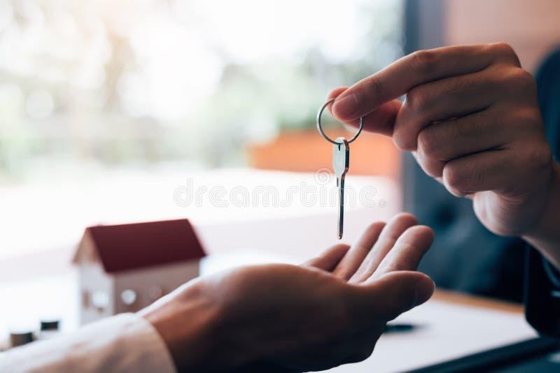 家庭代理的接近的手实施钥匙给新的购房者 免版税库存图片